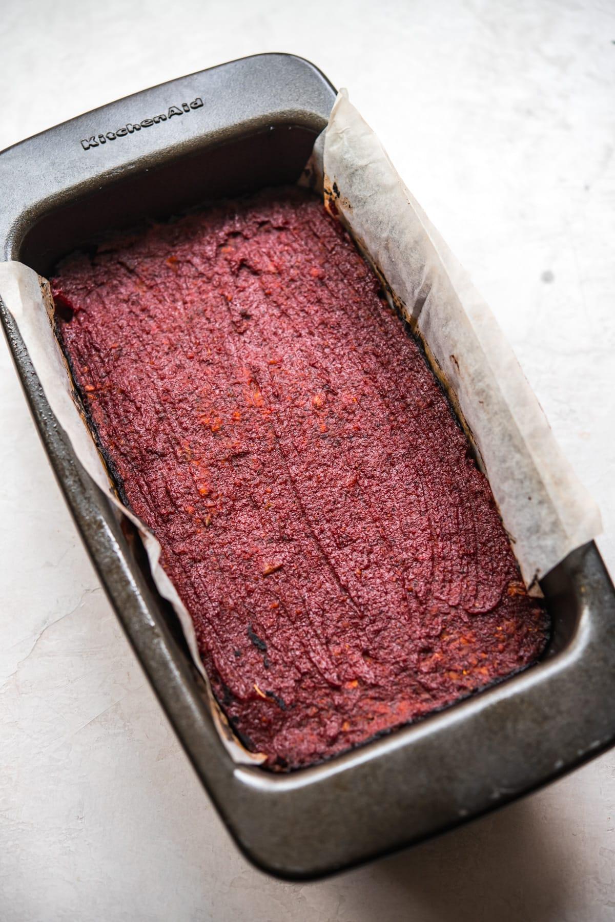 side view of baked vegan meatloaf in a loaf pan.