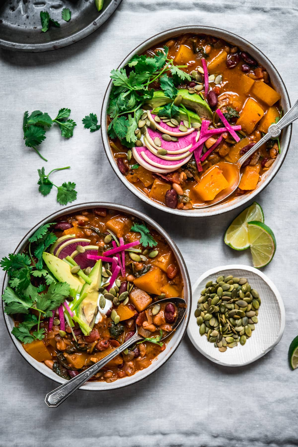 overhead view of bowls of vegan pumpkin chili topped with avocado slices, sour cream, pumpkin seeds and watermelon radish.