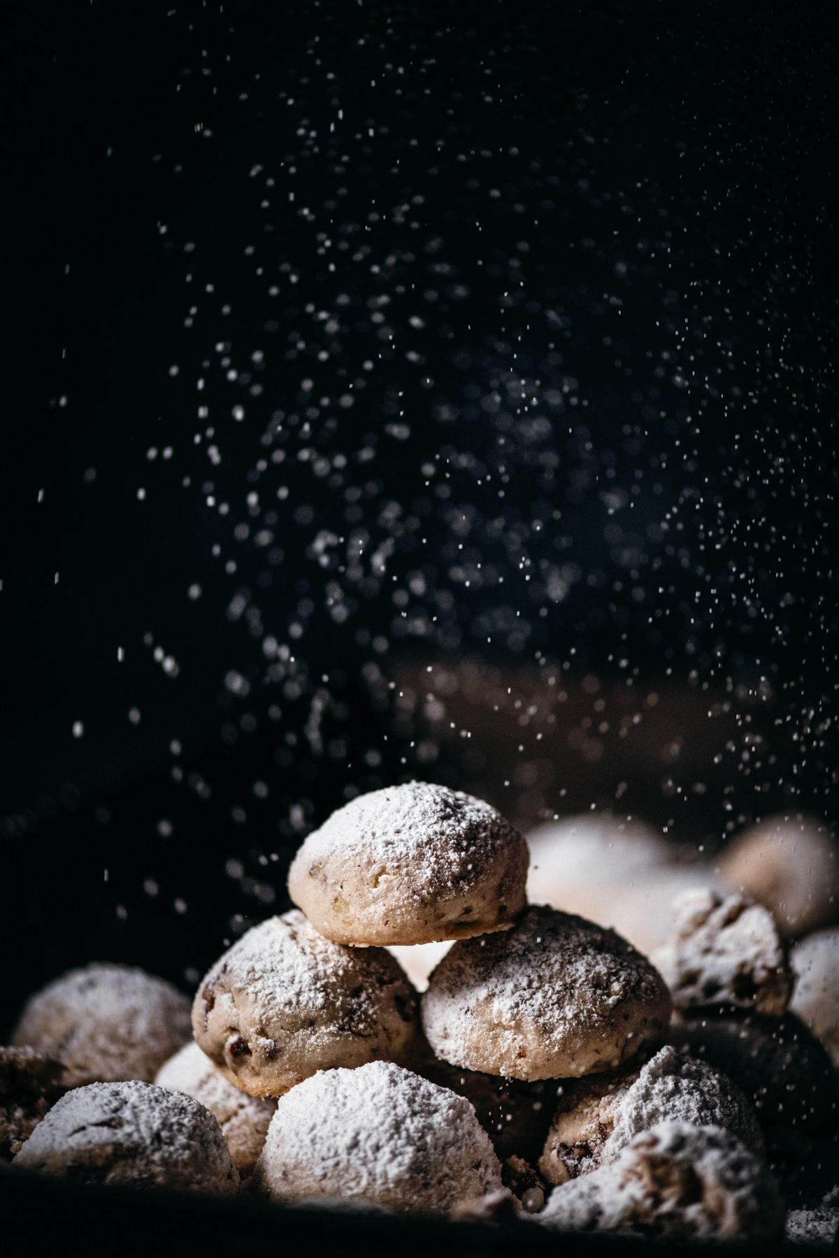 stack of pecan snowball cookies being dusted with powdered sugar.