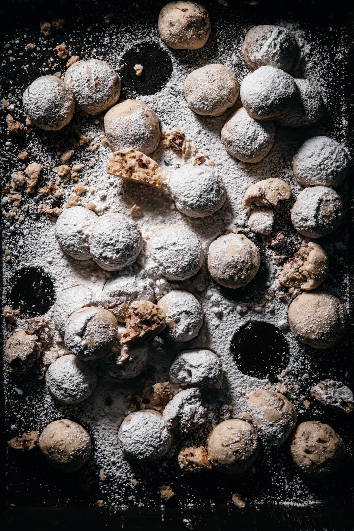 overhead view of vegan pecan snowball cookies on dark cookie sheet.