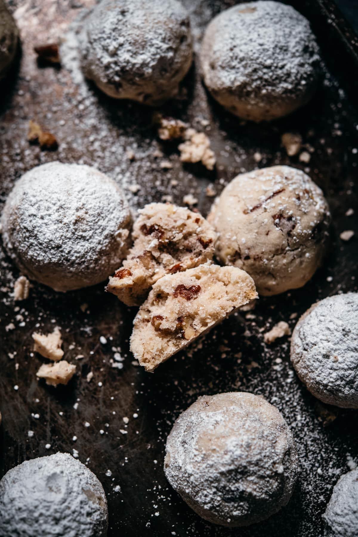 vegan and gluten free pecan snowball cookies with one broken in half to show interior.