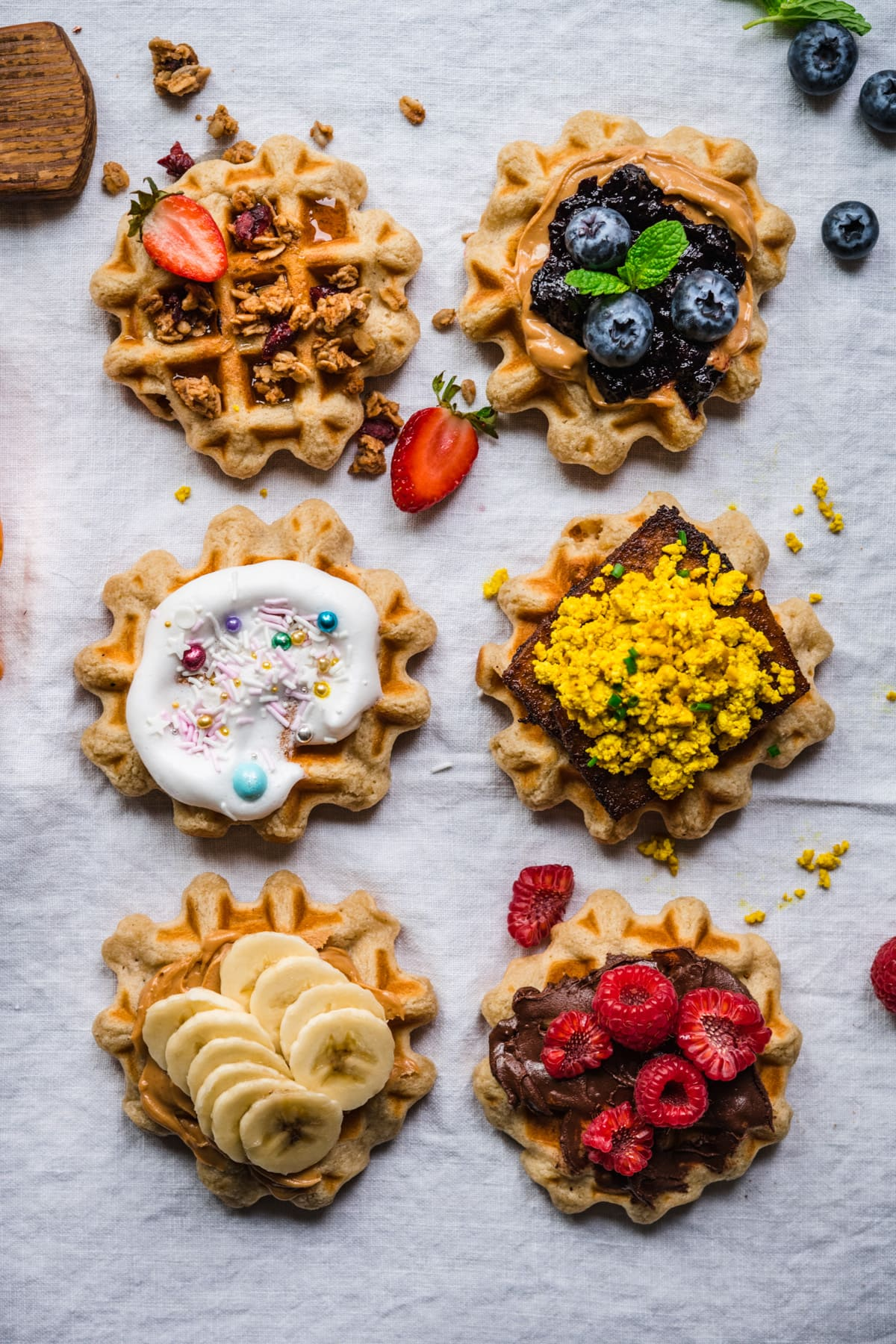 overhead view of 6 homemade waffles with different toppings.