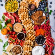 overhead view of loaded build your own waffle board with homemade waffles, fruit and toppings.
