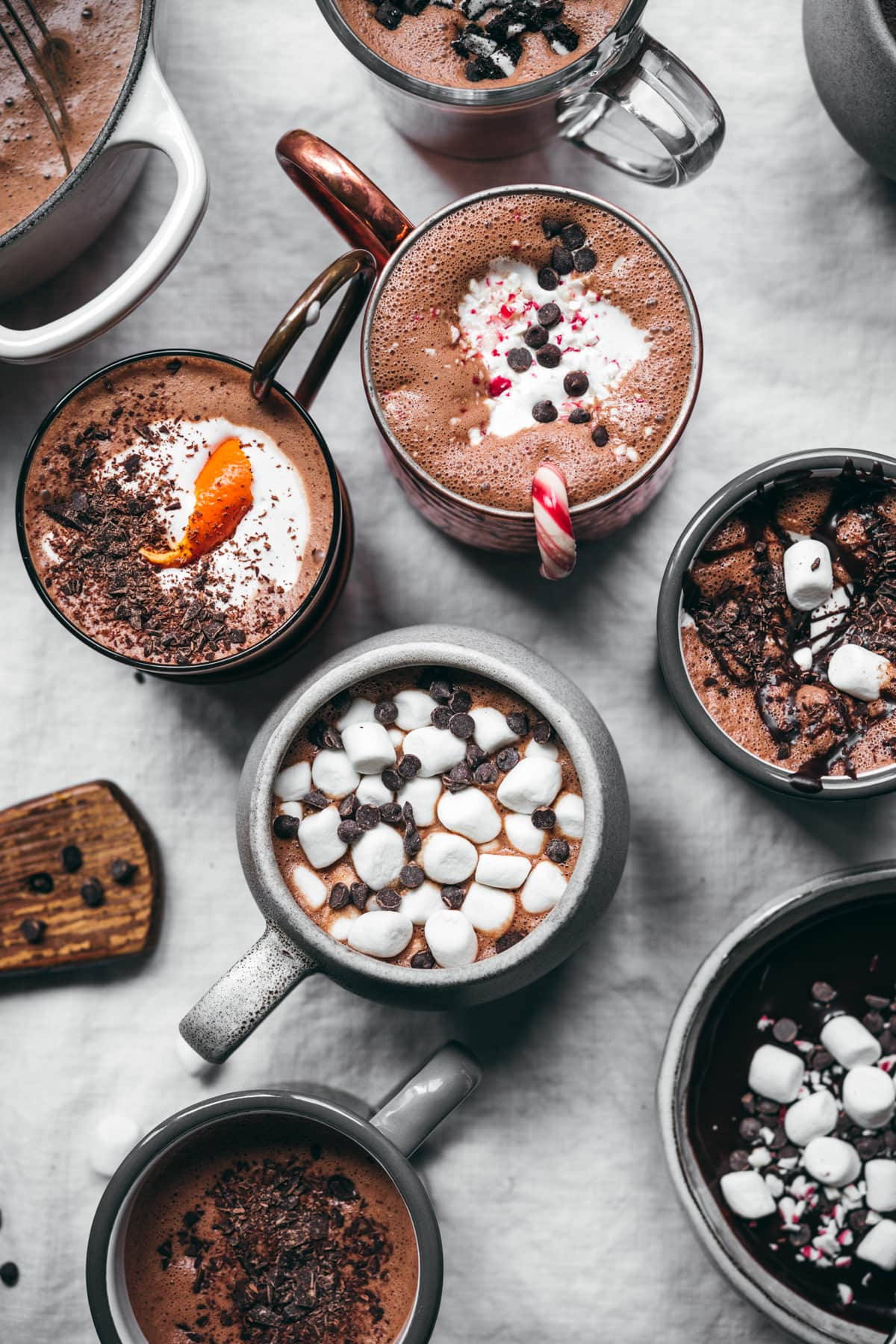 overhead view of vegan hot cocoa 5 ways in different mugs.