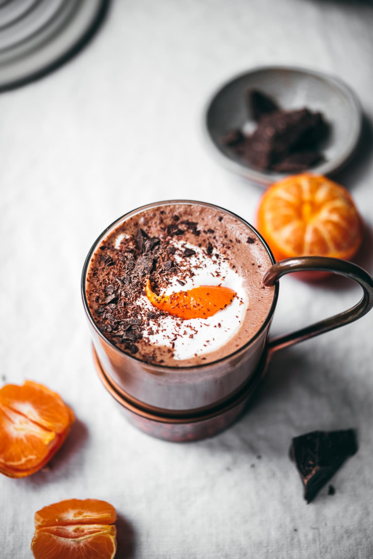close up view of vegan bourbon orange hot chocolate topped with chocolate shavings and orange peel.