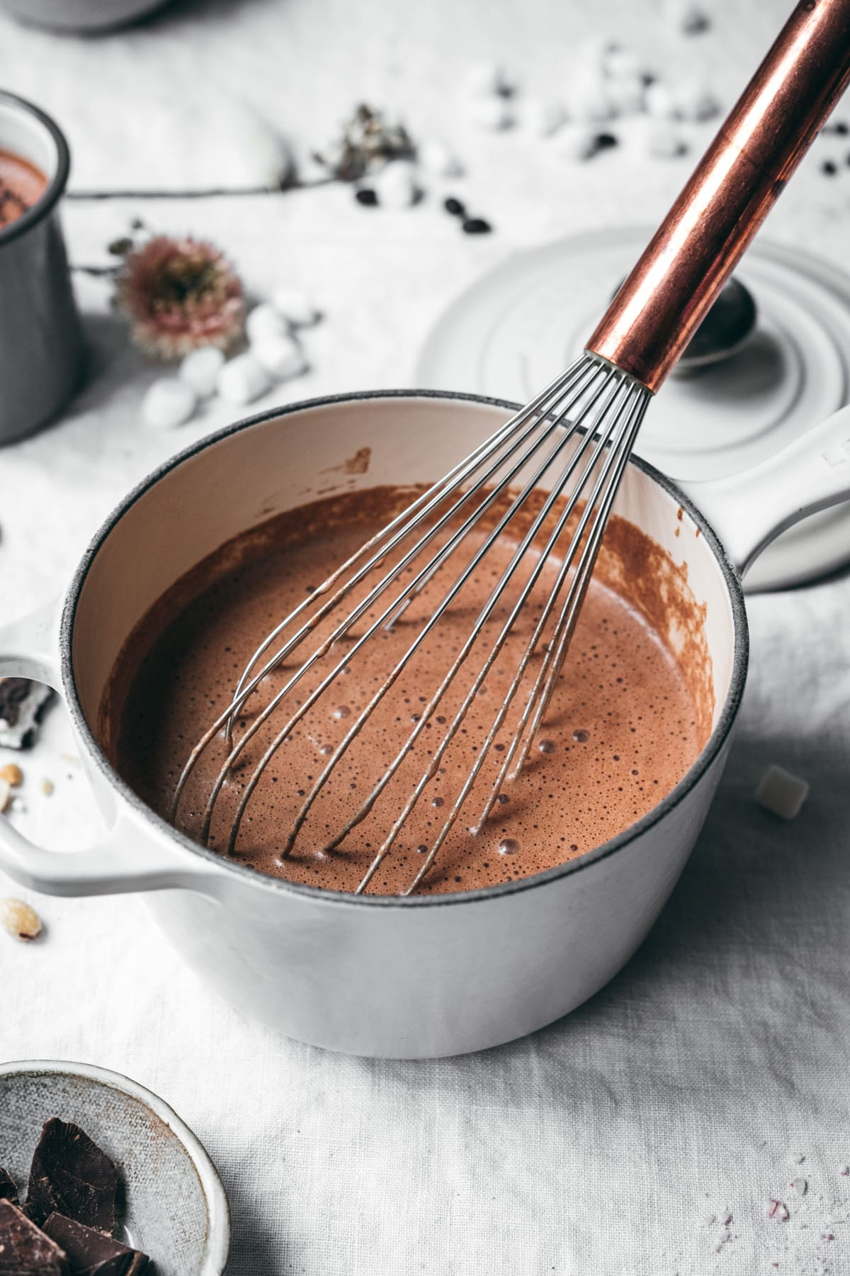 side view of mocha hot chocolate in a white saucepan with whisk.