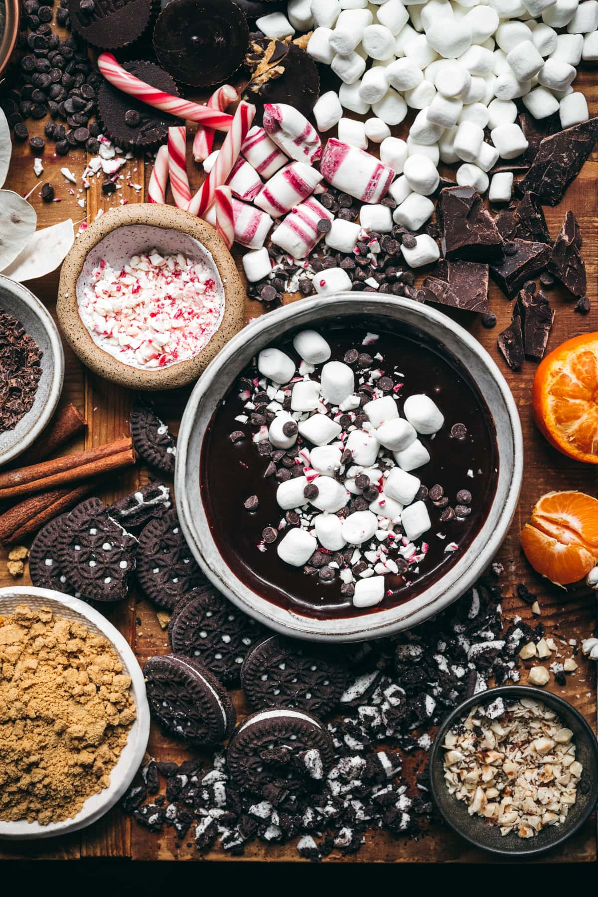 overhead view of hot cocoa board with lots of toppings like chocolate, marshmallows, peppermint, cookies, etc.