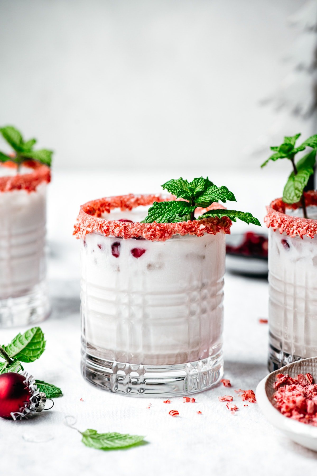 close up side view of vegan peppermint white russian cocktail with candy cane rim and fresh mint garnish.