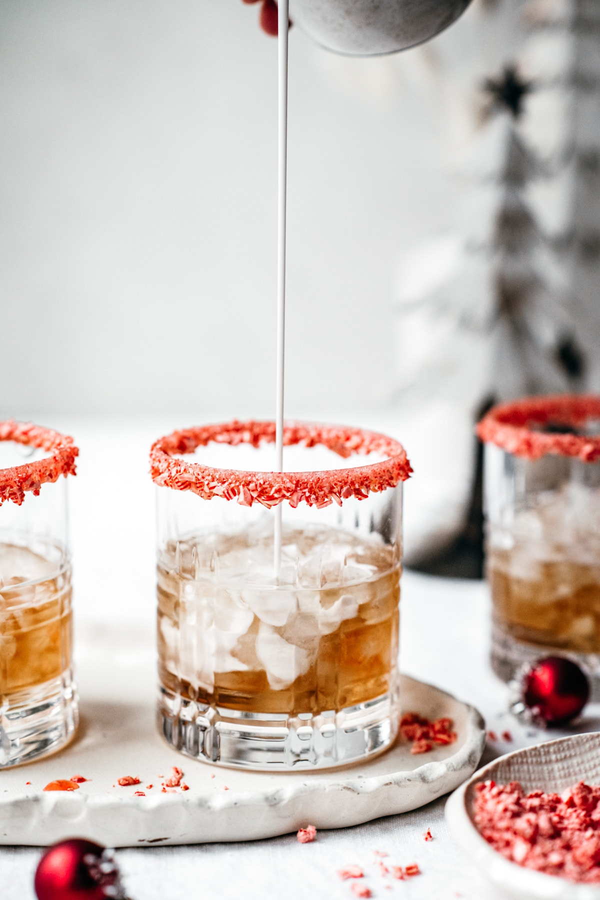 pouring cream into white russian cocktail with candy cane rim.