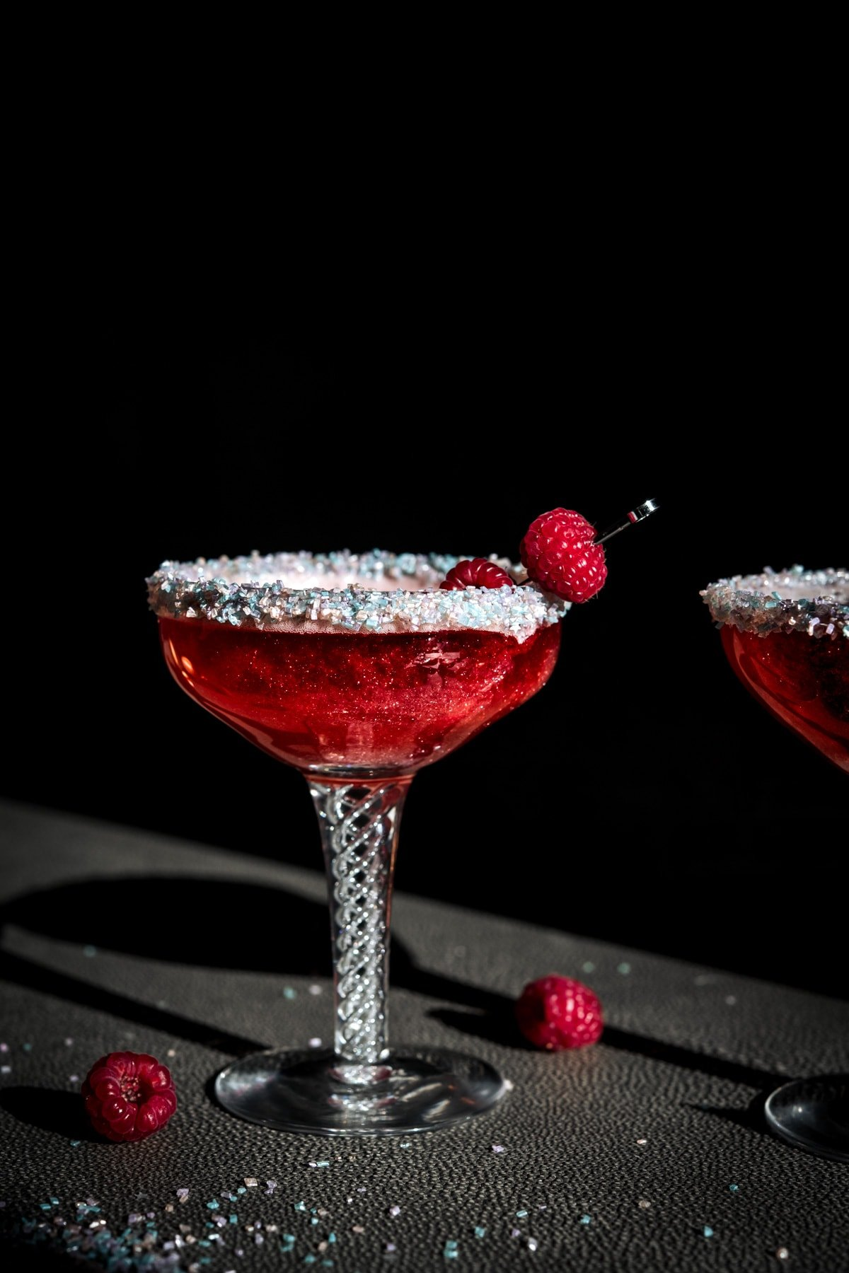 close up side view of shimmery raspberry rosé cocktail with sprinkle rim in antique cocktail glass.