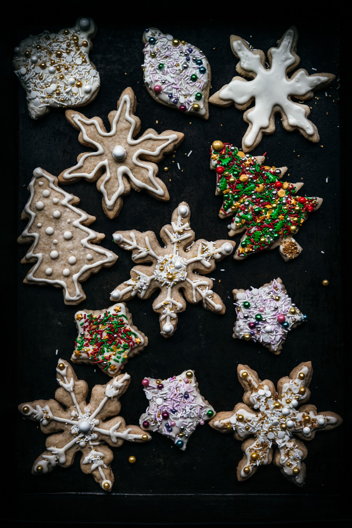 overhead view of sugar cookies in snowflake, christmas tree and star shapes.