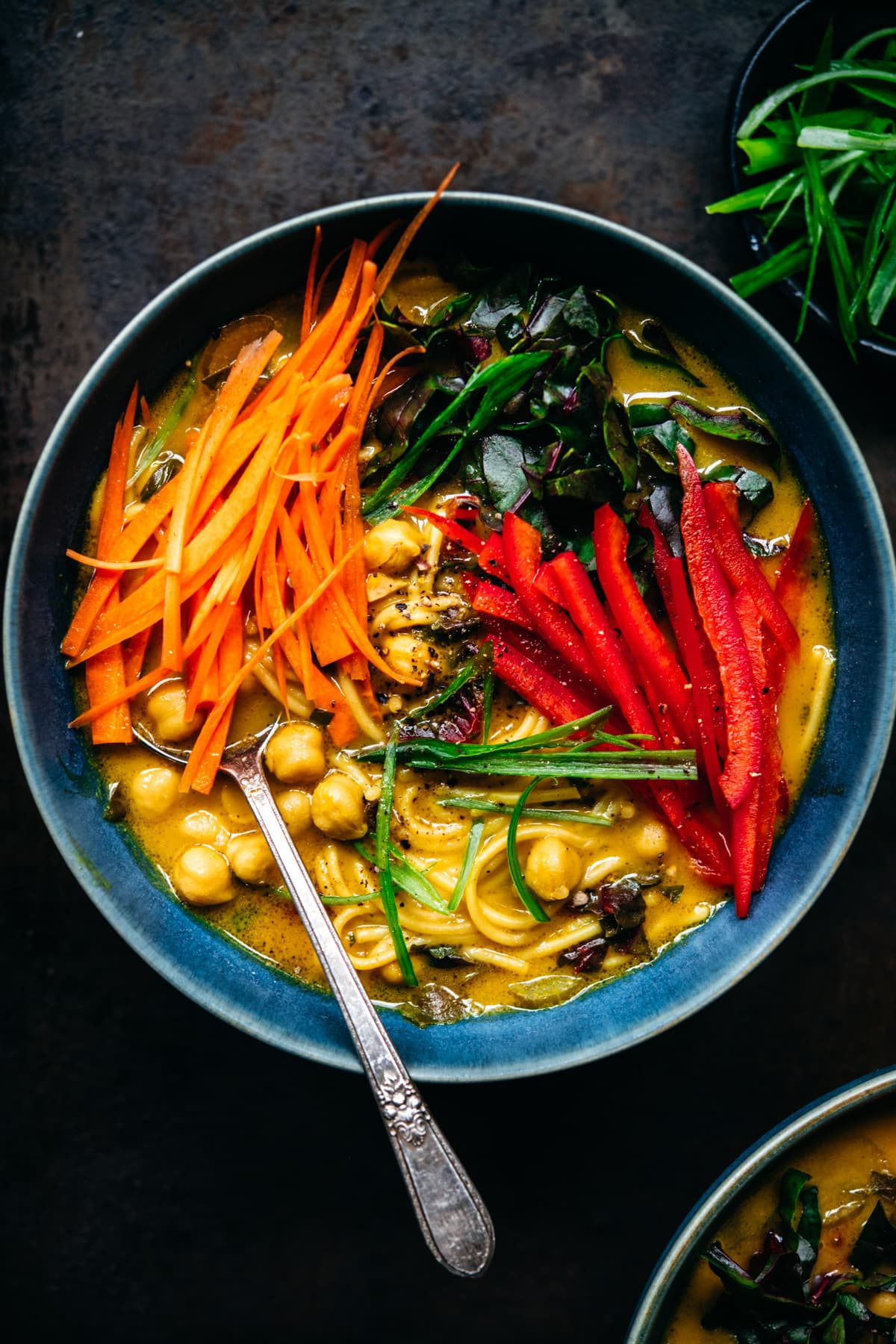 overhead view of immune boosting turmeric chickpea noodle soup in a blue soup bowl.