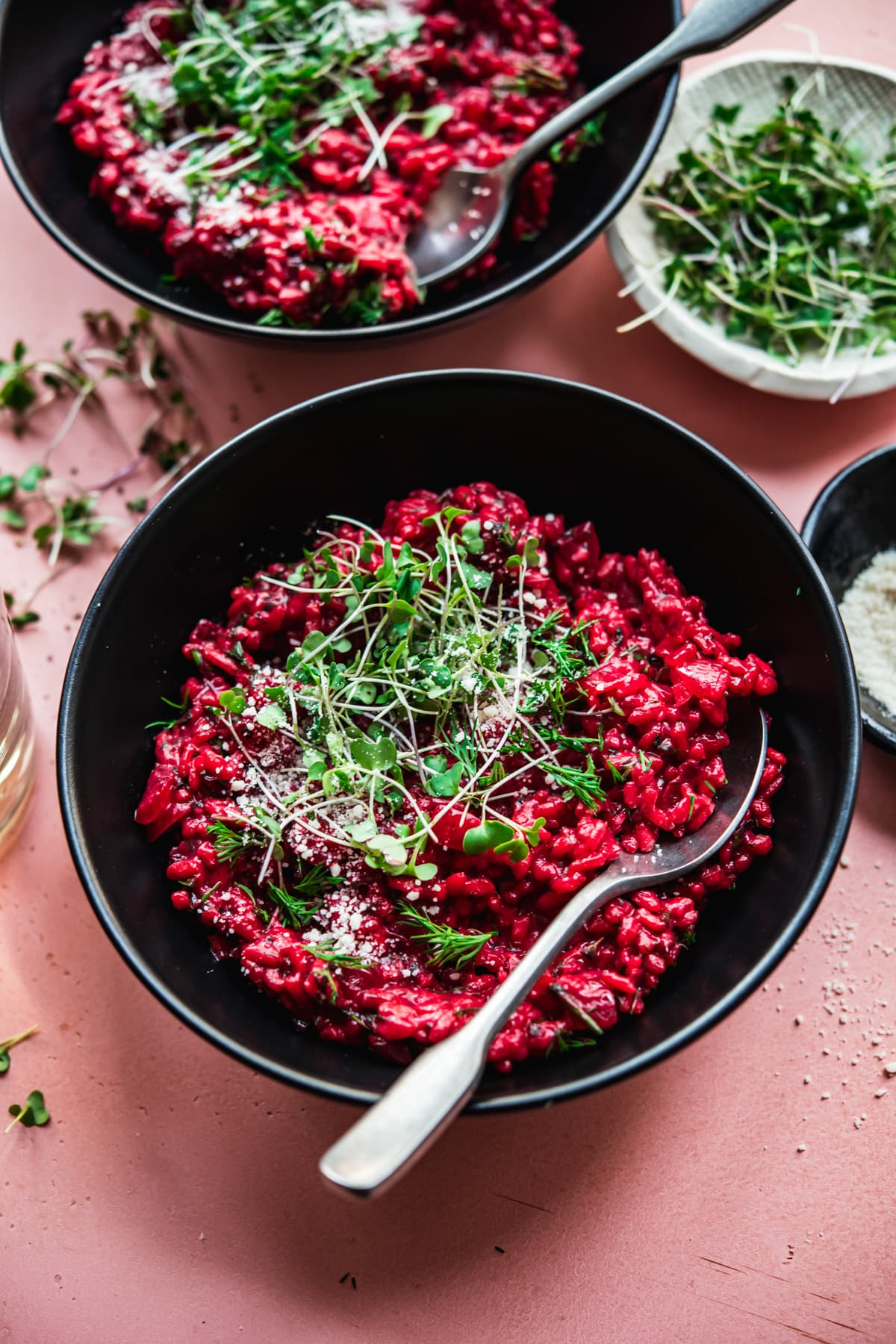 close up view of vegan beet risotto topped with microgreens and vegan parmesan.