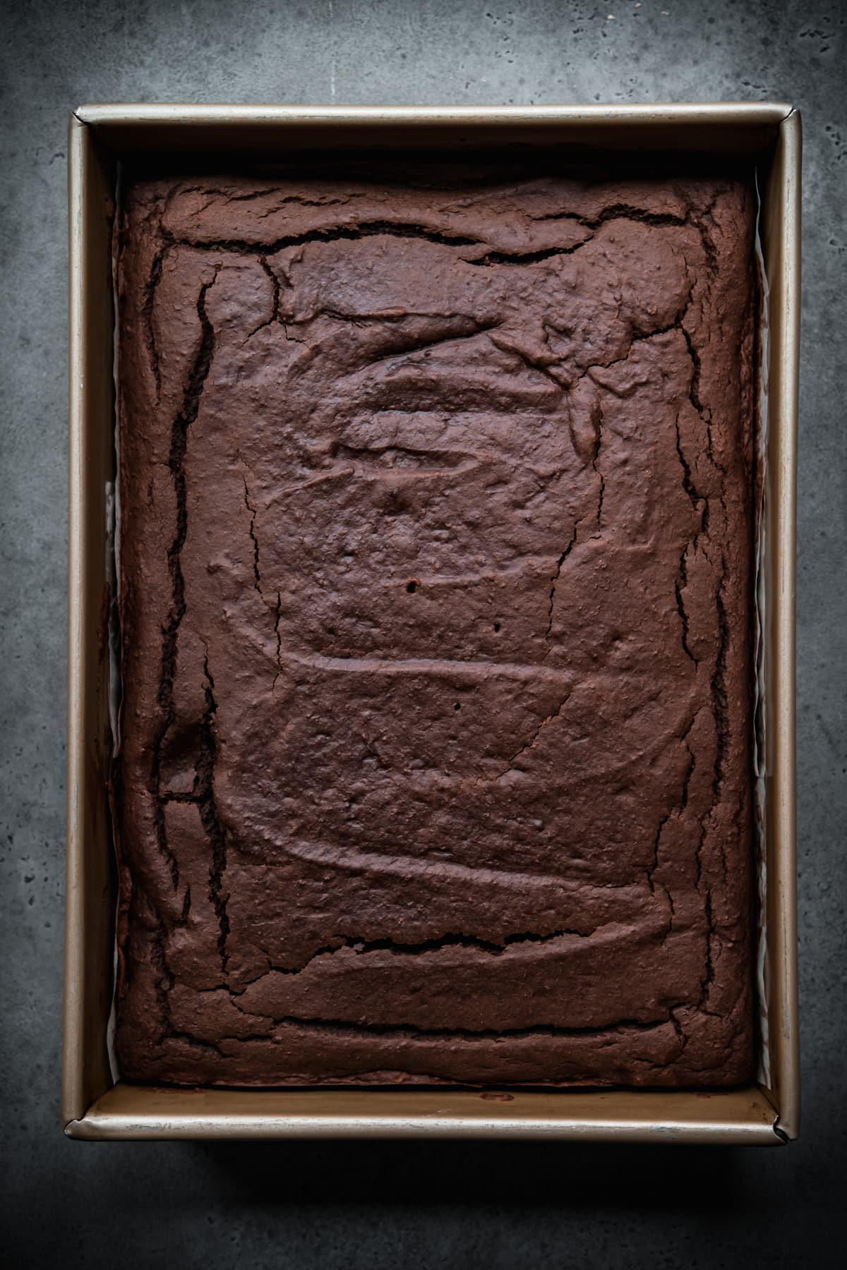 overhead view of baked vegan gluten free chocolate cake in a pan.
