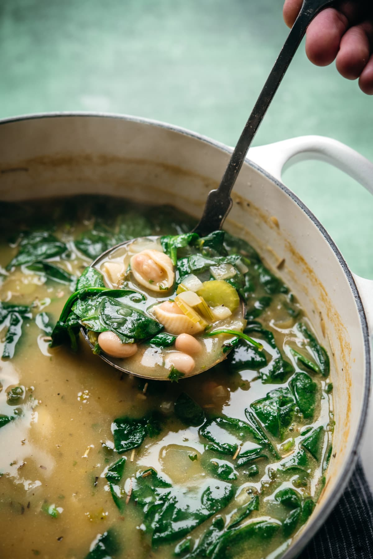 close up view of person holding ladle of white bean spinach soup above soup pot.