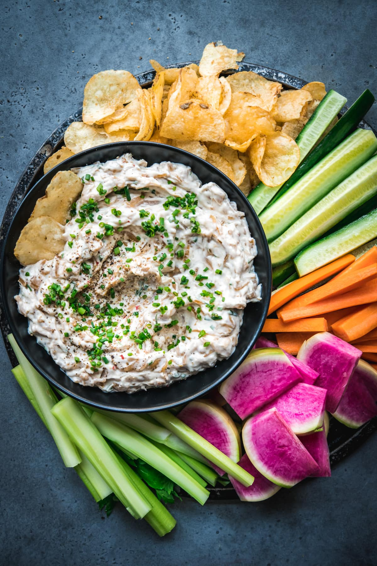 overhead view of vegan caramelized onion dip on a platter with chips and vegetables.