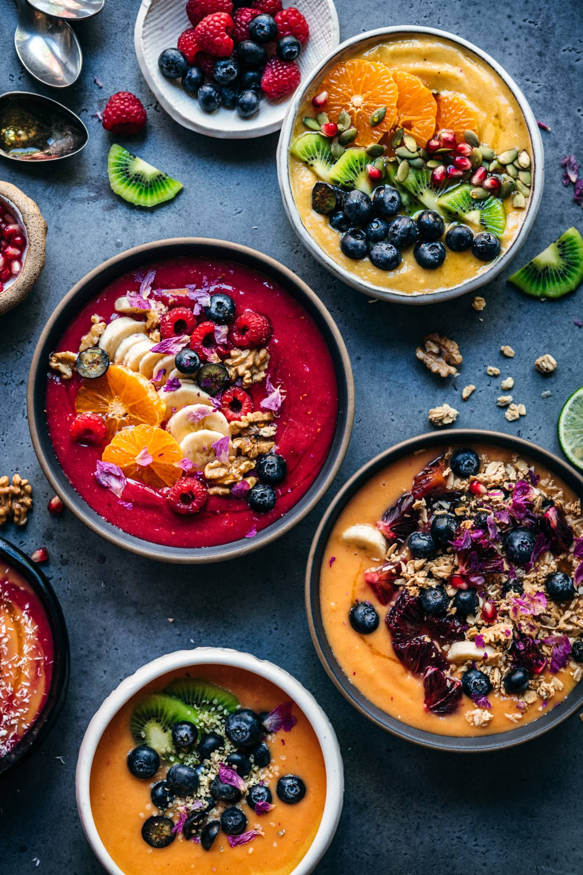 overhead view of multiple red, orange and yellow smoothie bowls with fresh fruit and granola toppings.