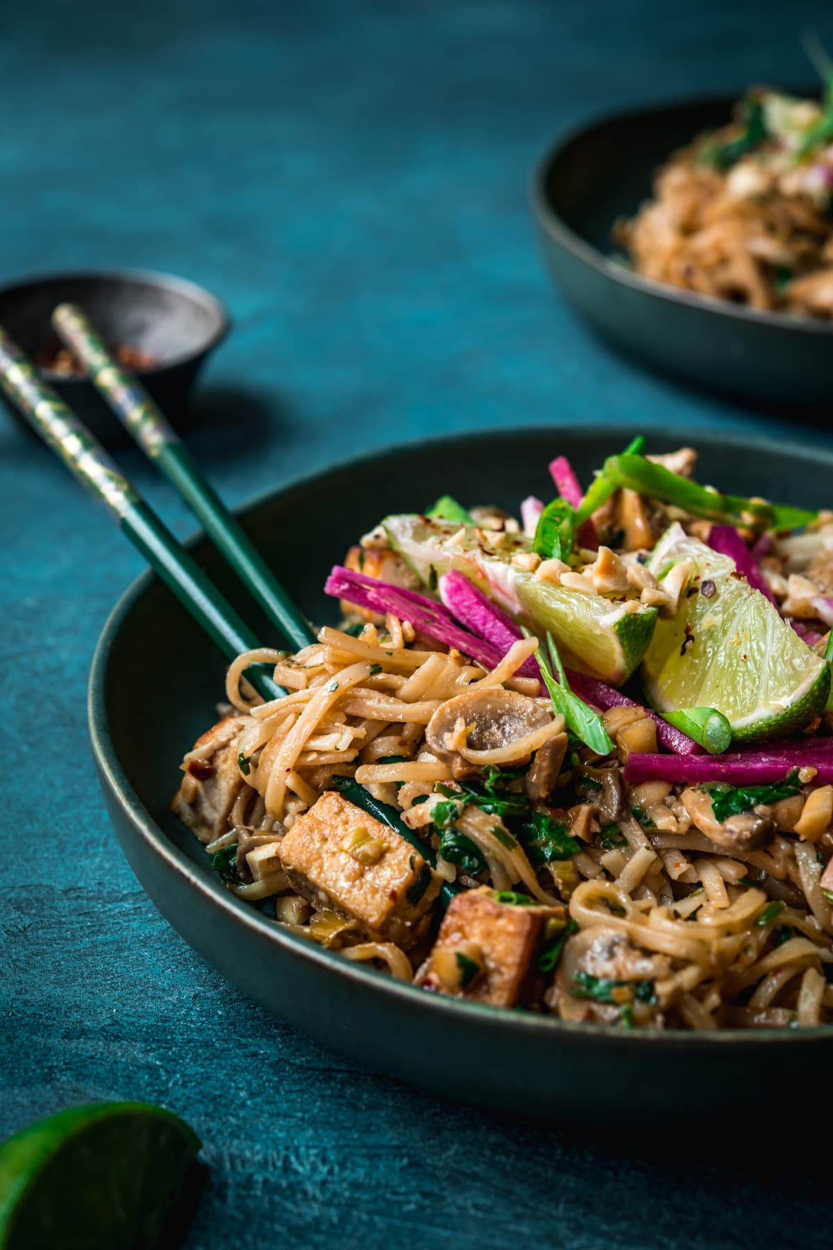 close up view of vegan pad thai with rice noodles, tofu and mushrooms.