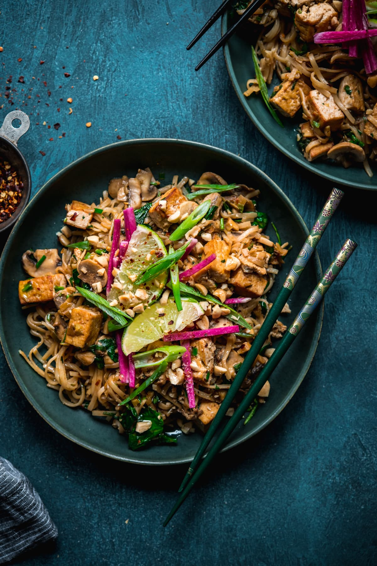 overhead view of vegan pad thai with tofu in a blue bowl with chopsticks.