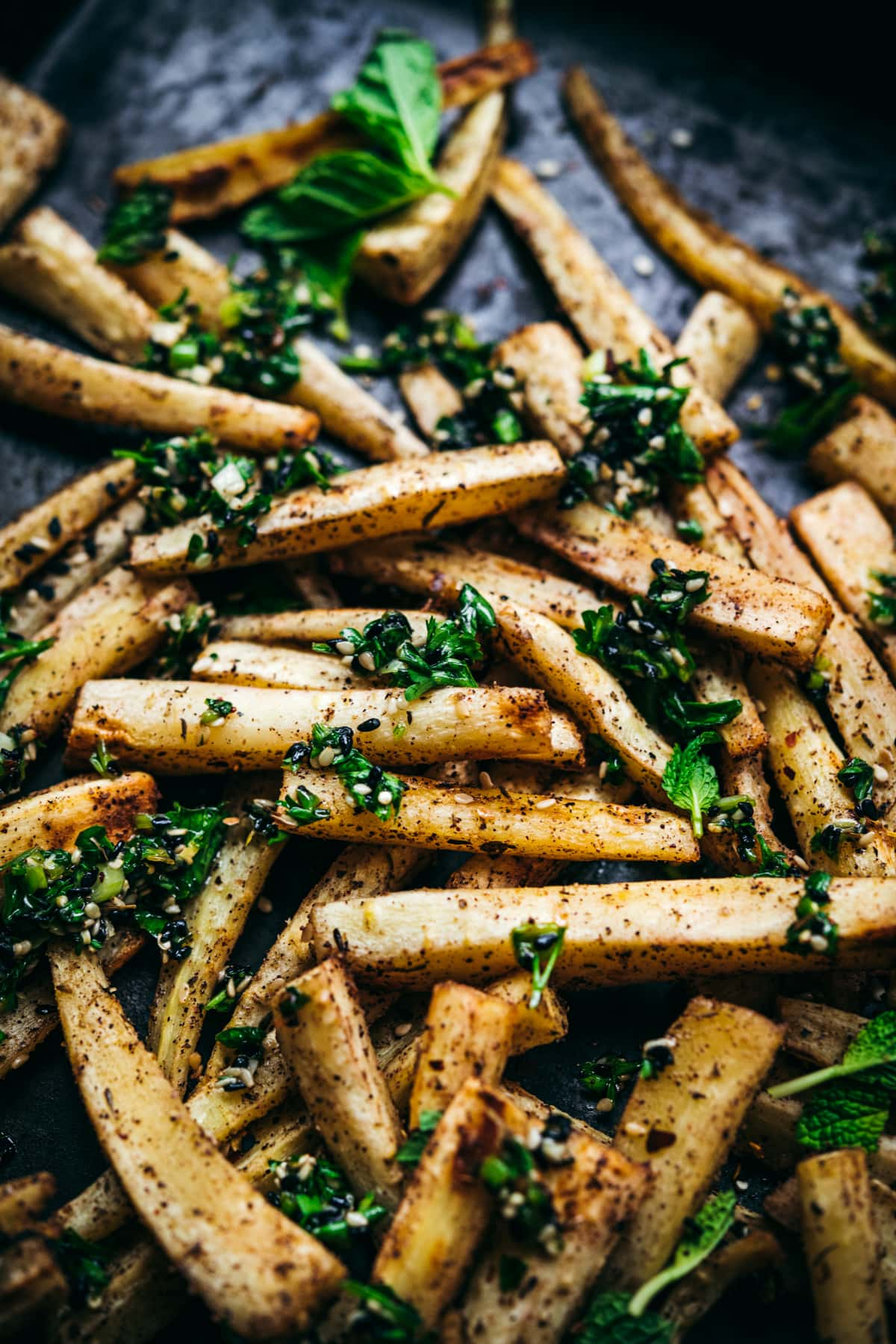 close up view of roasted parsnips on a sheet pan with za'atar gremolata on top.