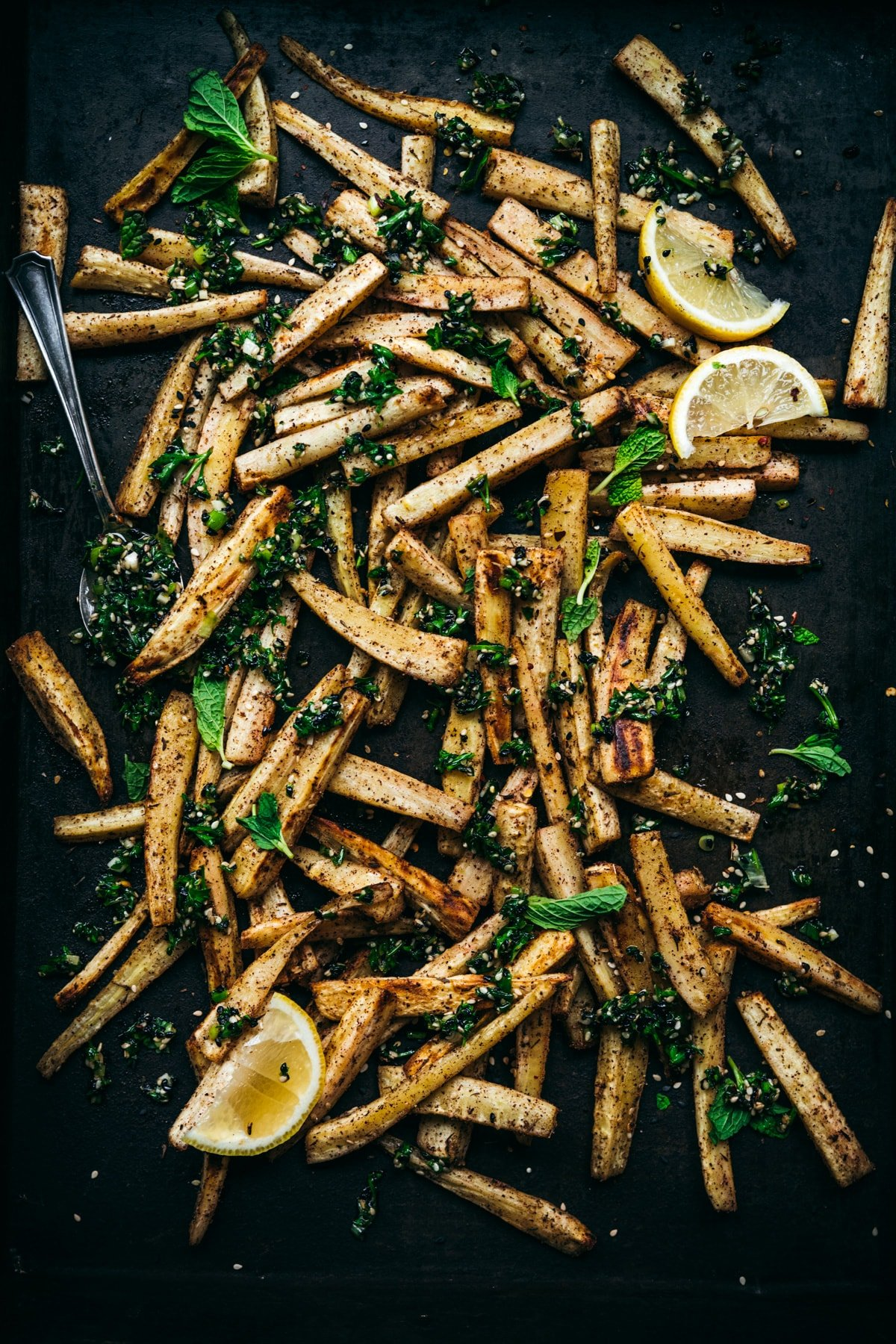 overhead view of roasted parsnips on a sheet pan with za'atar gremolata on top.