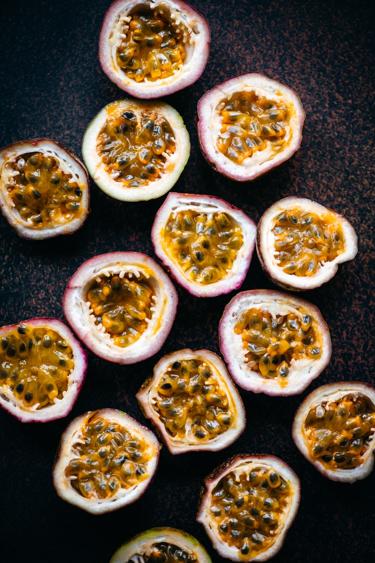 overhead view of fresh passion fruit halves on dark background.