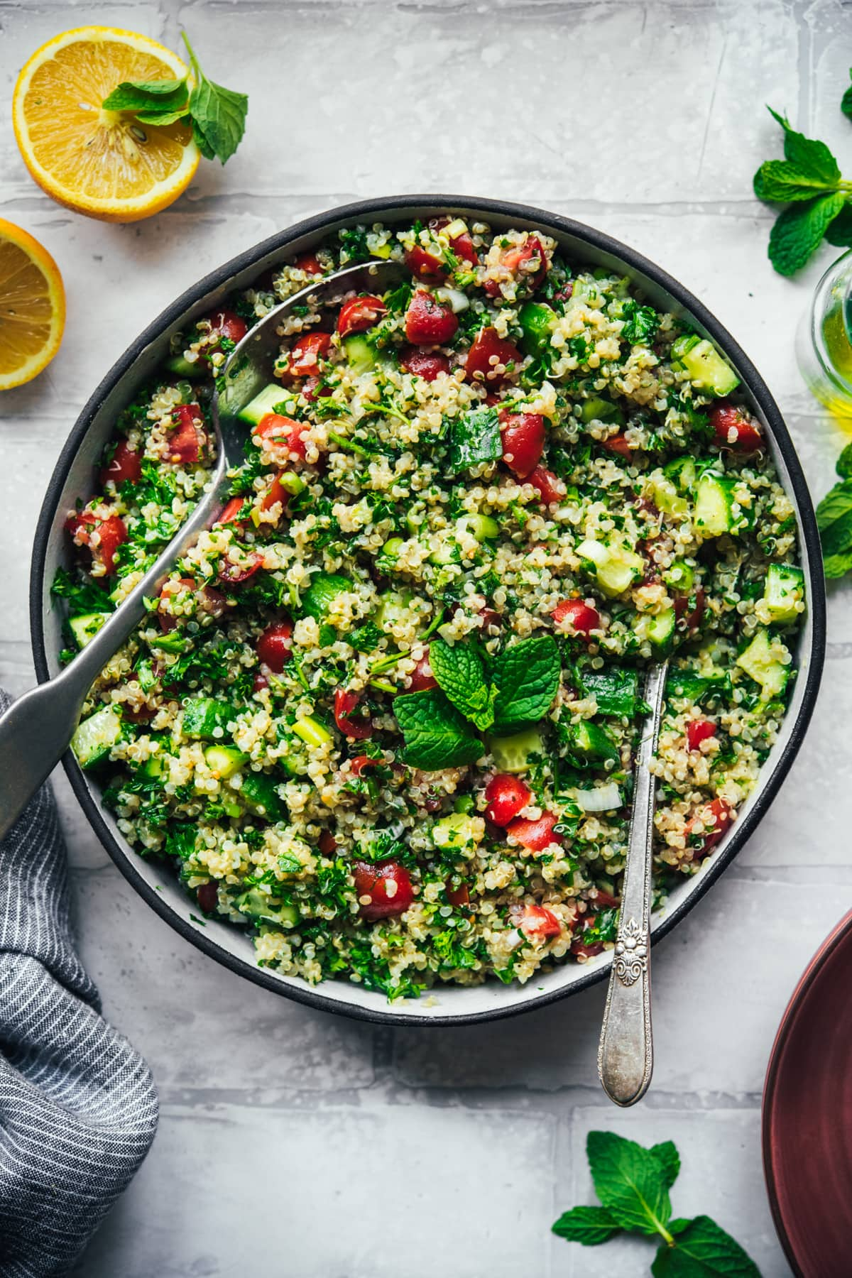 overhead view of vegan quinoa tabbouleh in a salad bowl with serving spoons.