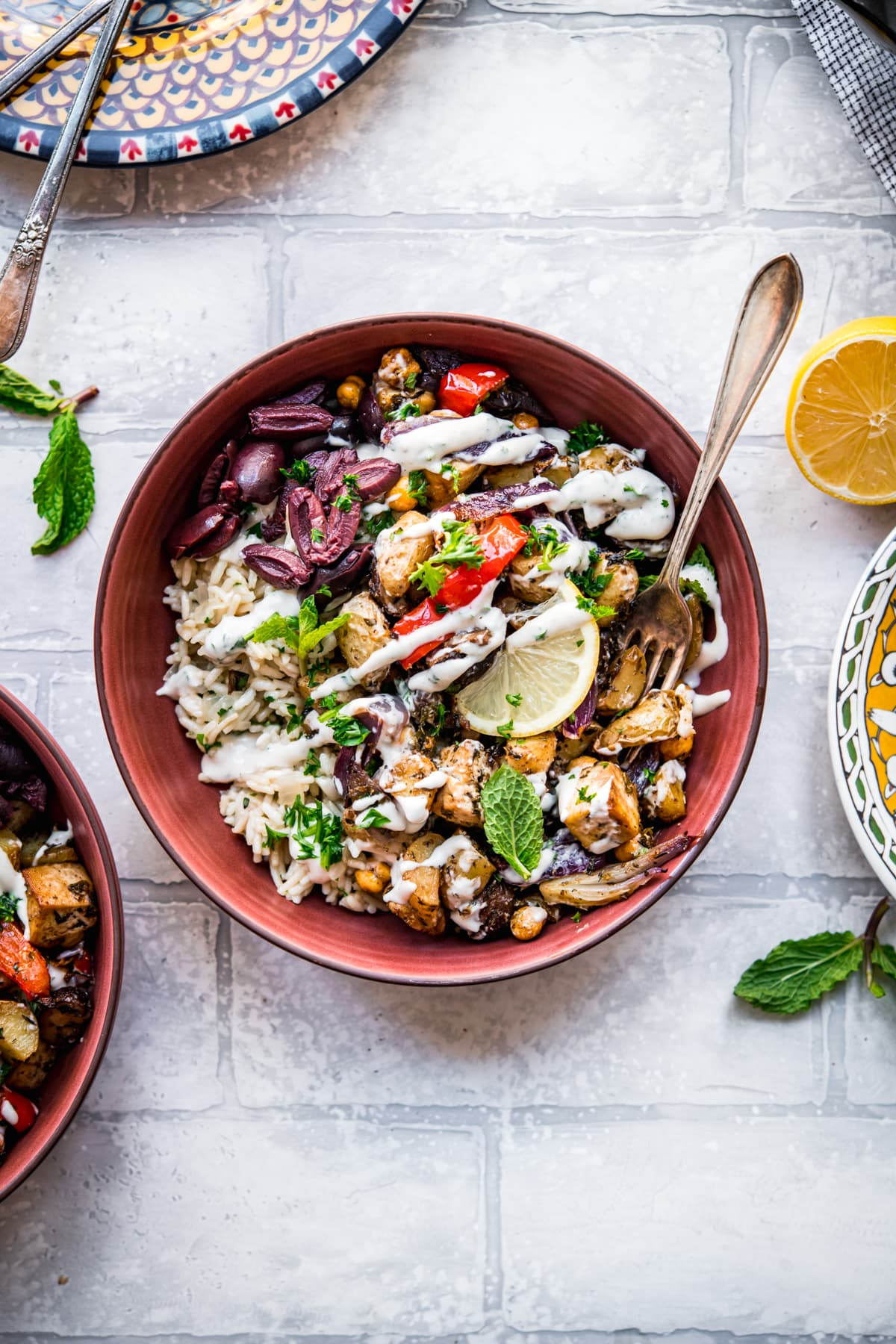 overhead view of Mediterranean roasted tofu and vegetables in a bowl over rice pilaf with yogurt tahini dressing.