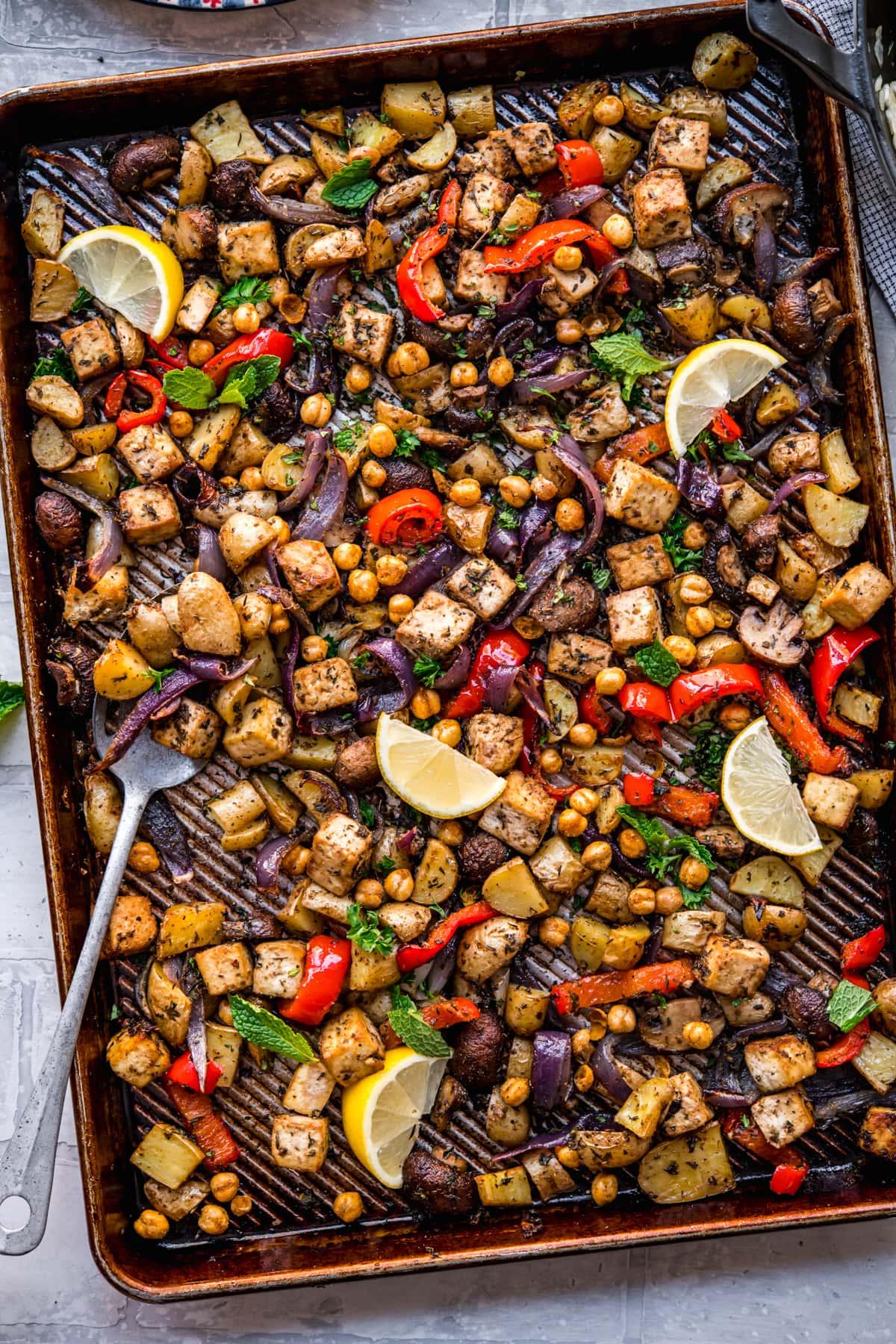 overhead view of vegan mediterranean sheet pan dinner with tofu, chickpeas and vegetables.