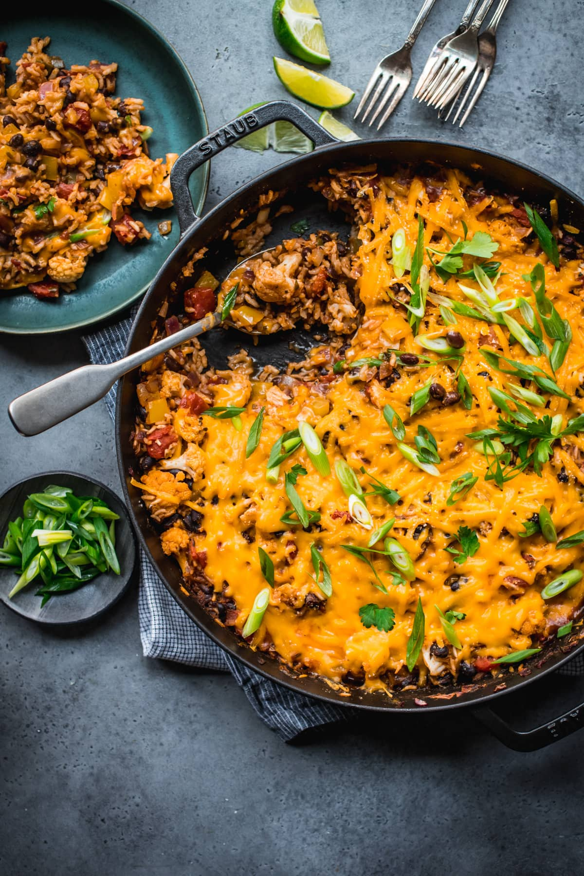 overhead view of vegan cheesy cauliflower bake with black beans and rice in large skillet.