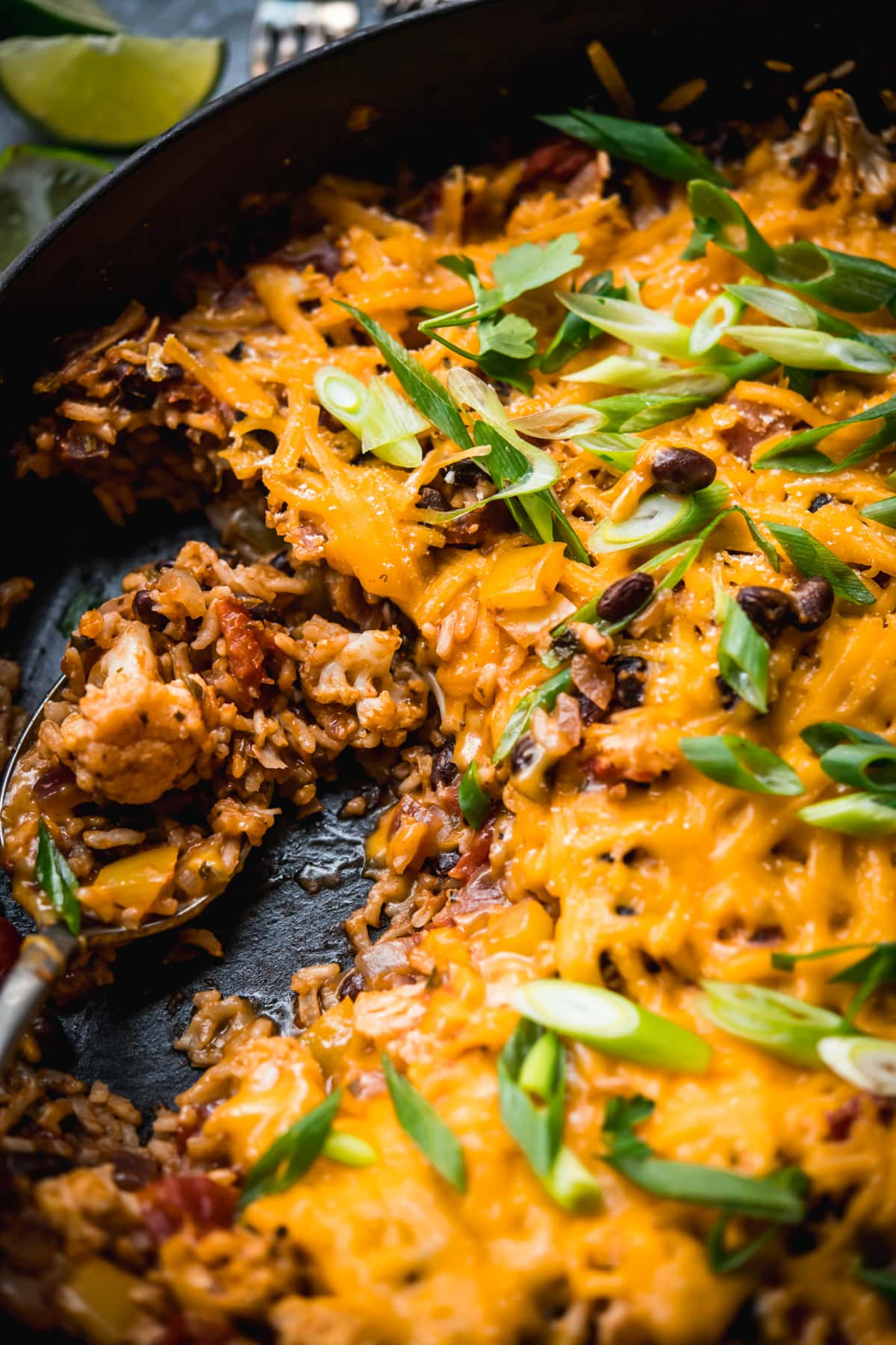 close up view of cheesy vegan cauliflower, rice and black bean bake in a skillet.