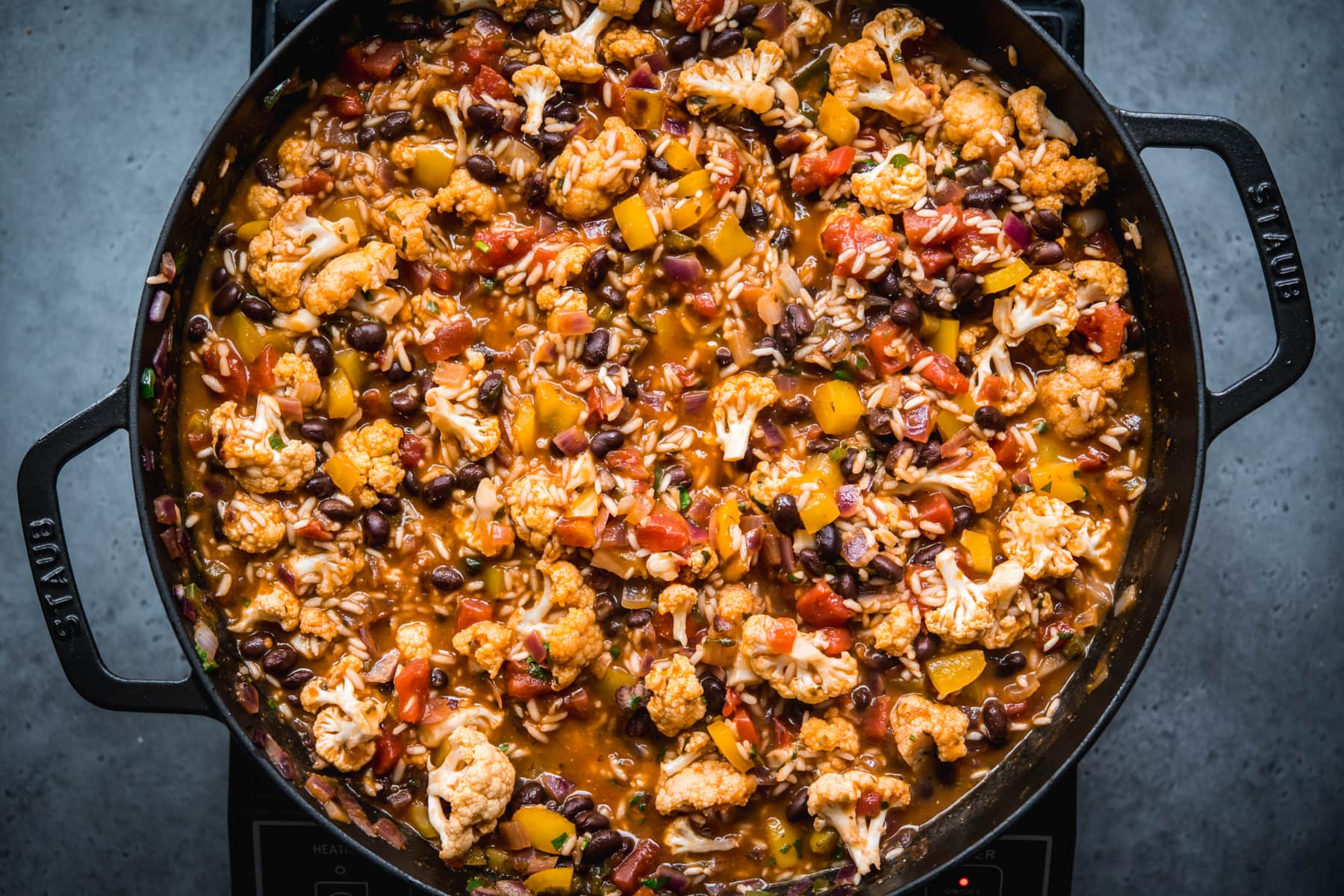 overhead view of cauliflower black bean and rice bake in large skillet.