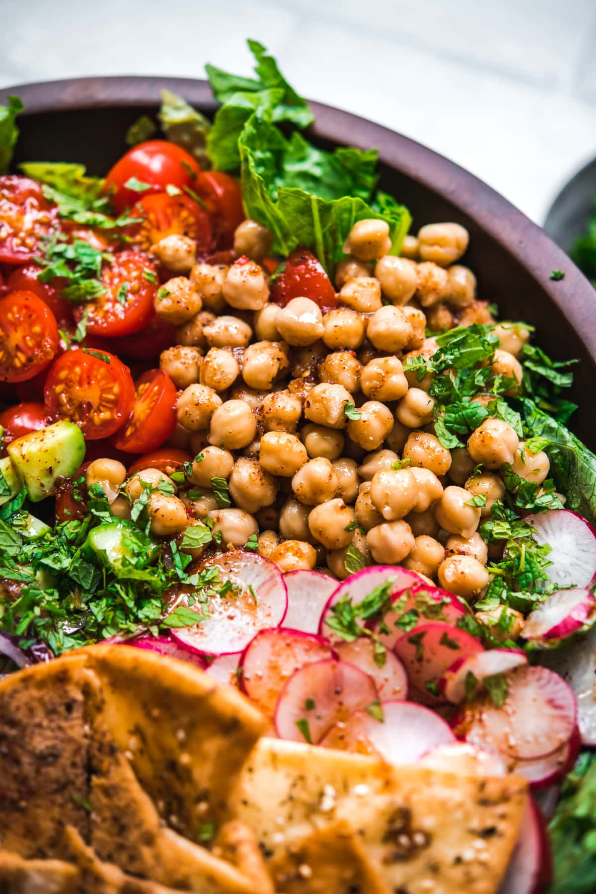close up view of chickpeas in sumac dressing on fattoush salad.