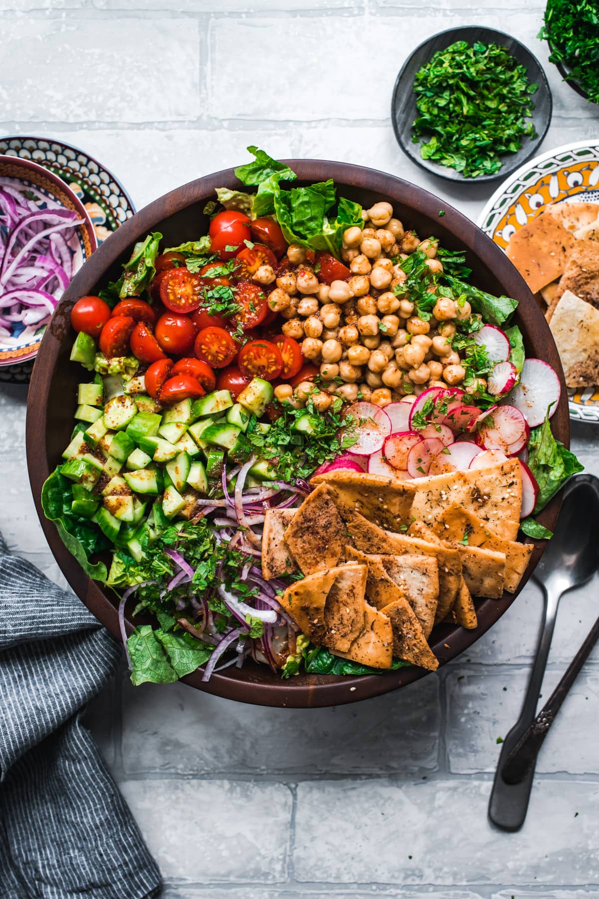 overhead view of chickpea fattoush salad with pita chips in wood salad bowl.