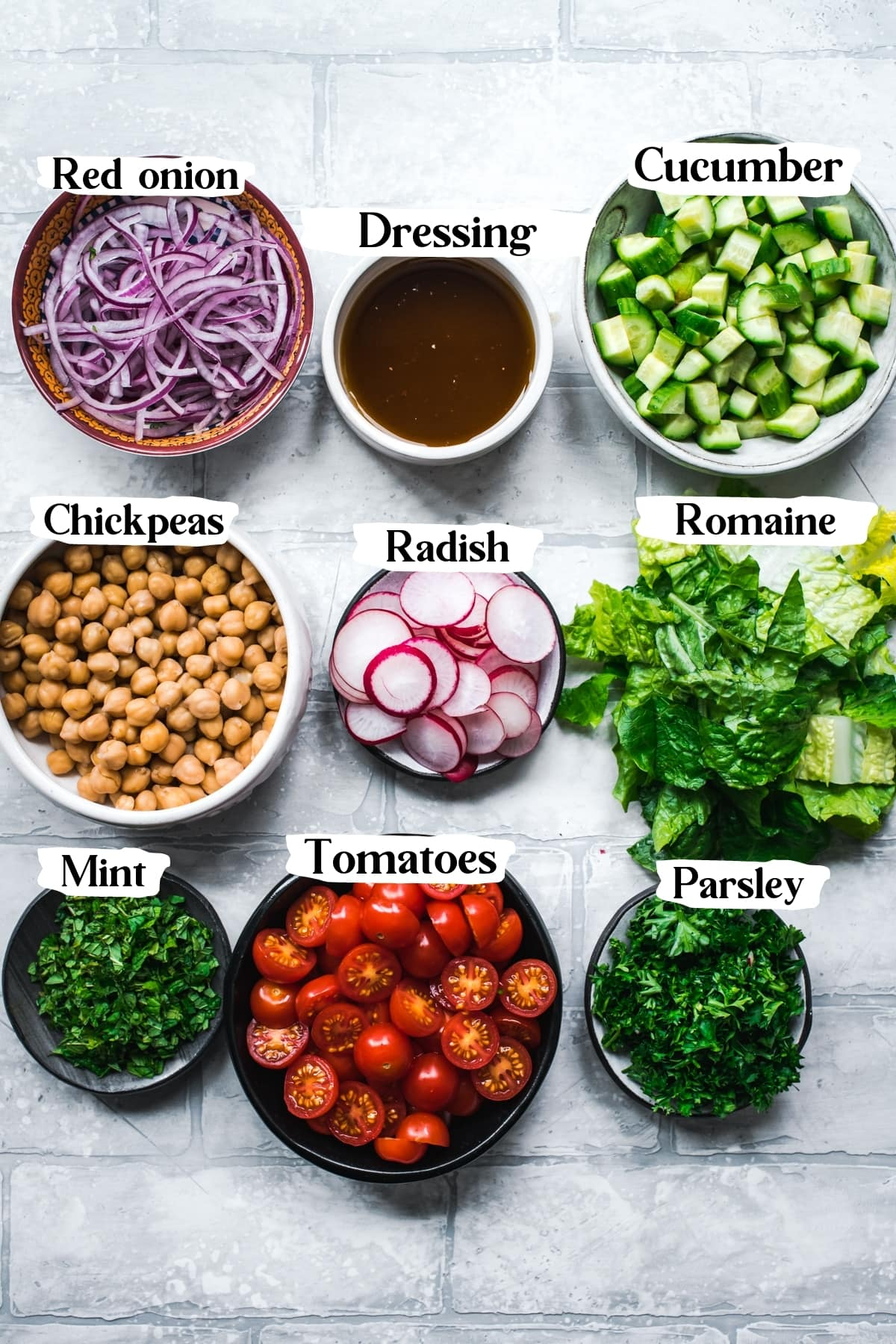overhead view of ingredients for chickpea fattoush salad in small bowls on tile backdrop.