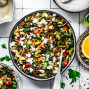overhead view of vegan french lentil salad in a large bowl with serving spoon on white tile background.
