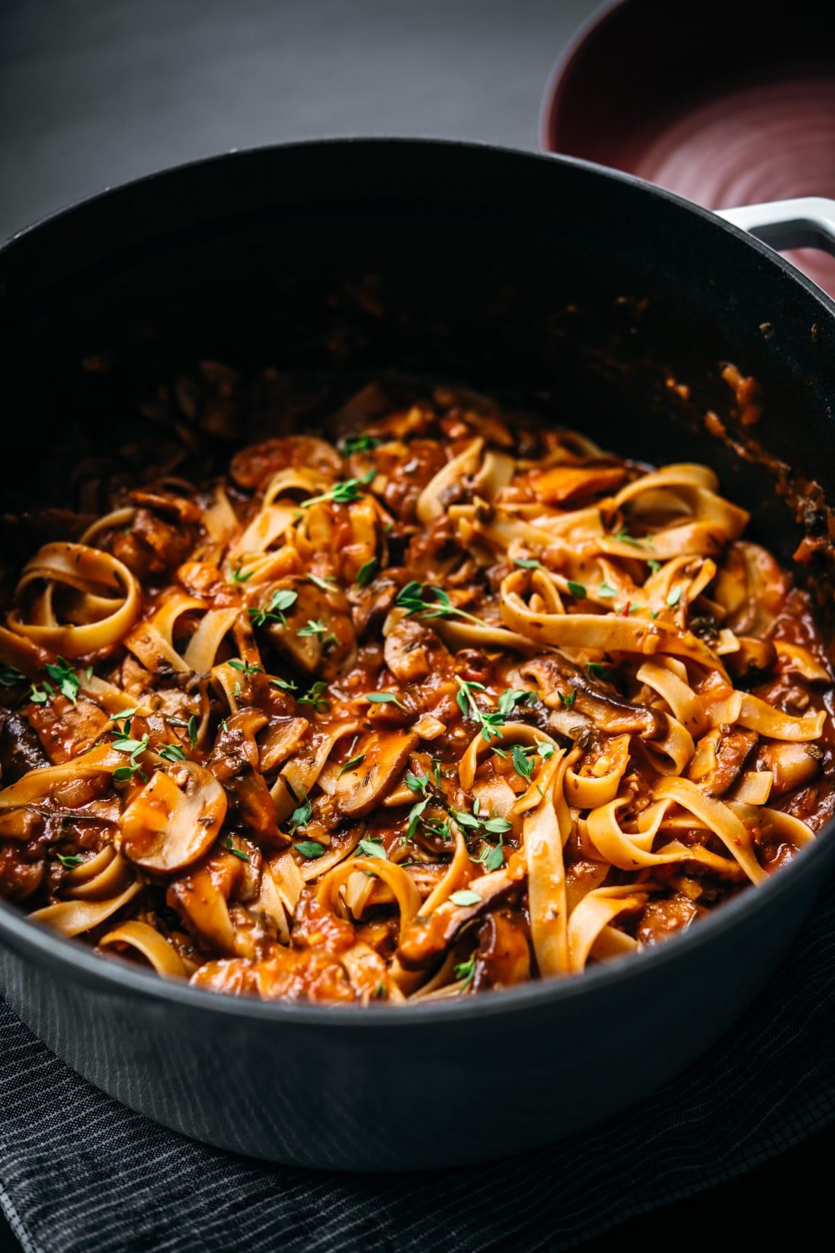 close up view of vegan mushroom ragu over pasta in a large white dutch oven.