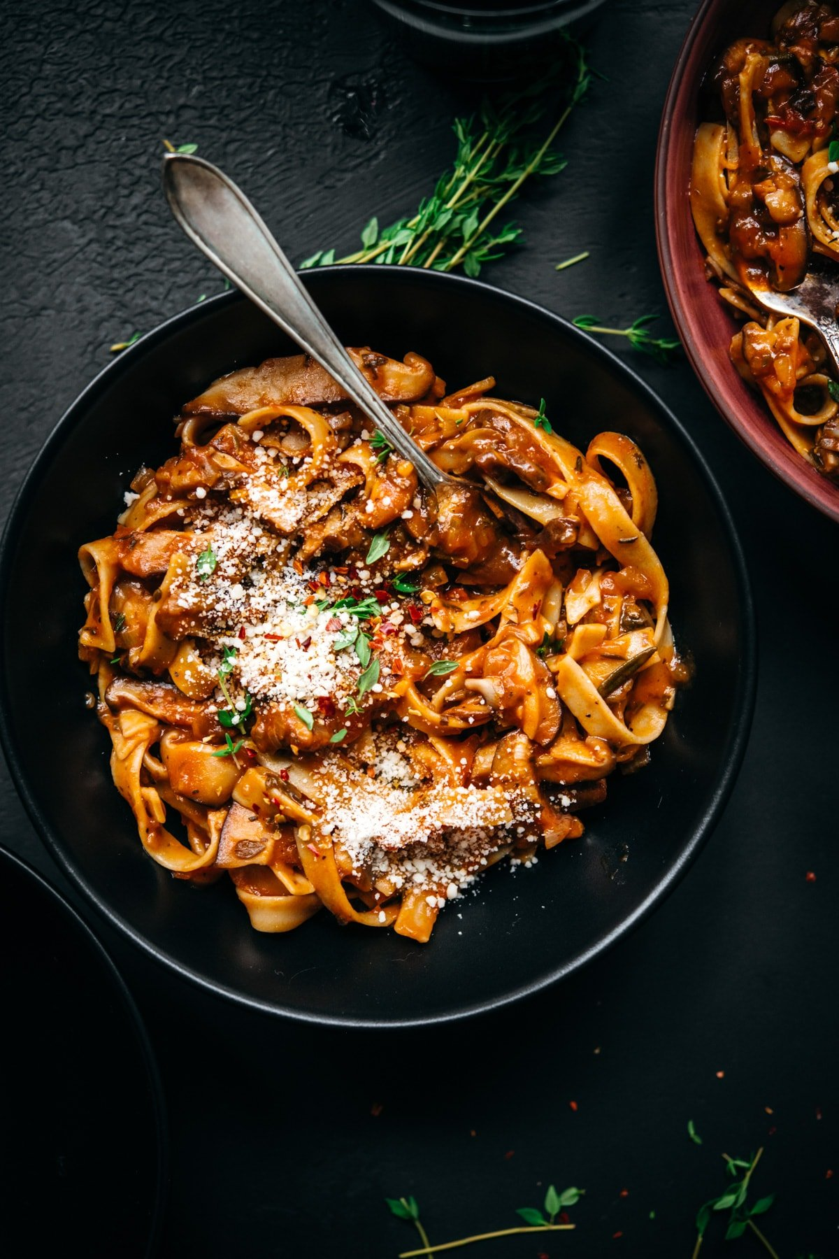 overhead view of vegan mushroom ragu over pasta in a black bowl.