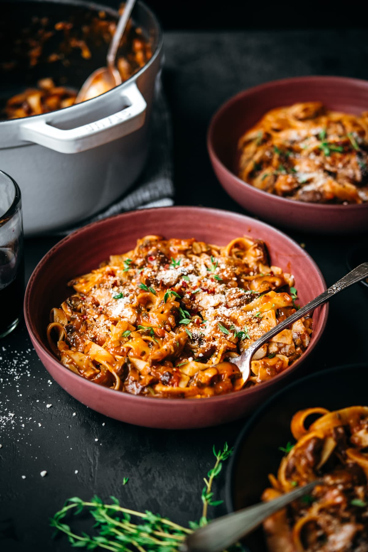 side view of vegan mushroom ragu over pasta in a red bowl.
