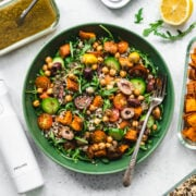 overhead view of quinoa arugula and sweet potato salad in a green bowl.