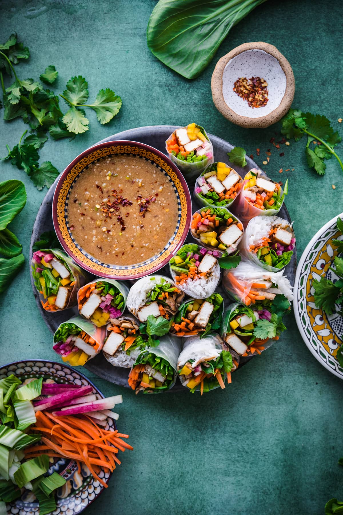 overhead view of tofu vegetable summer rolls on a circular platter with bowl of miso dipping sauce.