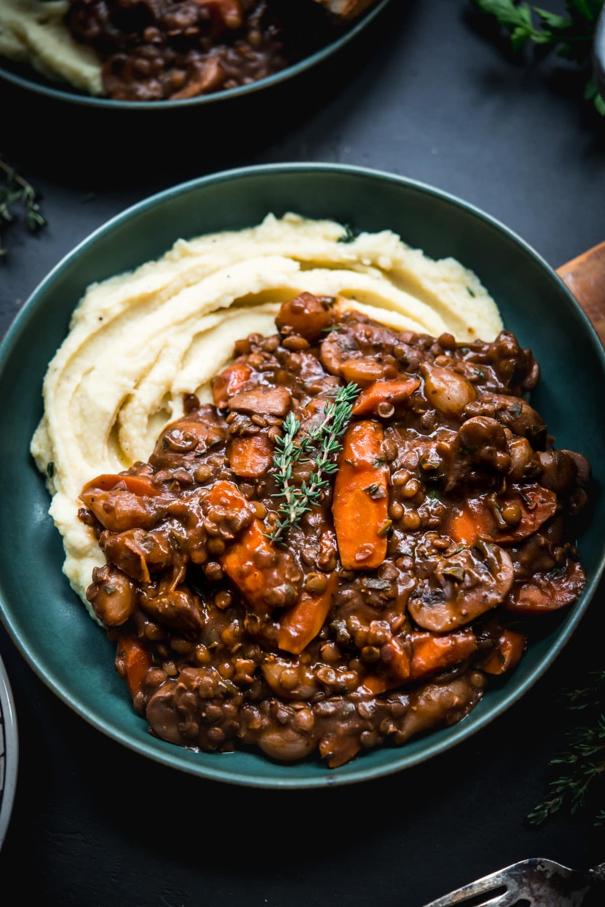 close up view of vegan lentil and mushrooom coq au vin over mashed potatoes in a bowl.