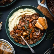 overhead view of vegan lentil and mushrooom coq au vin over mashed potatoes in a bowl.