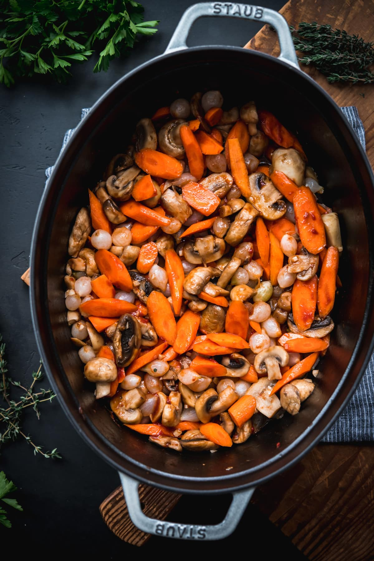 carrots, mushrooms and pearl onions being sautéed in a large dutch oven.