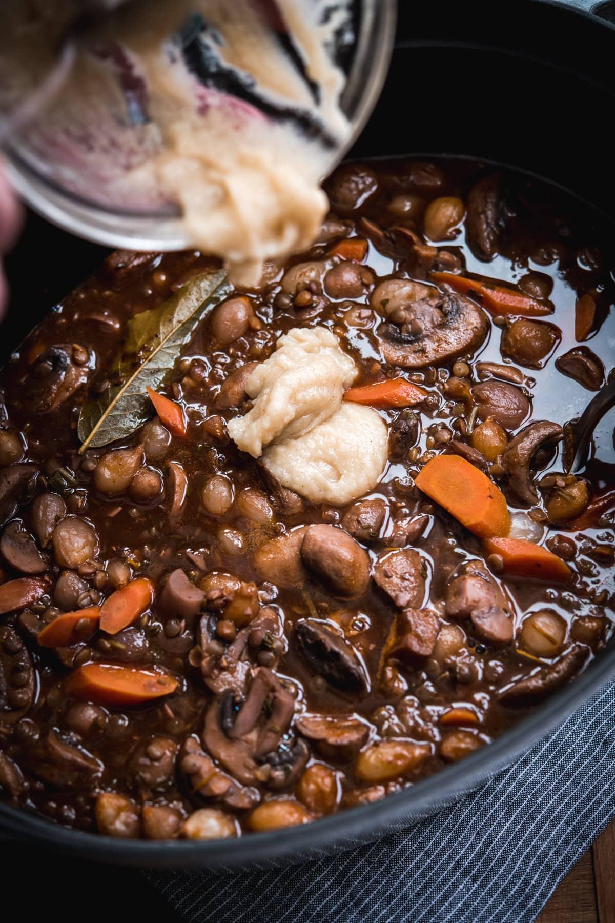 pouring roux into vegan coq au vin in a large pot.