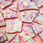overhead view of vegan white chocolate bark broken into pieces topped with sprinkles.