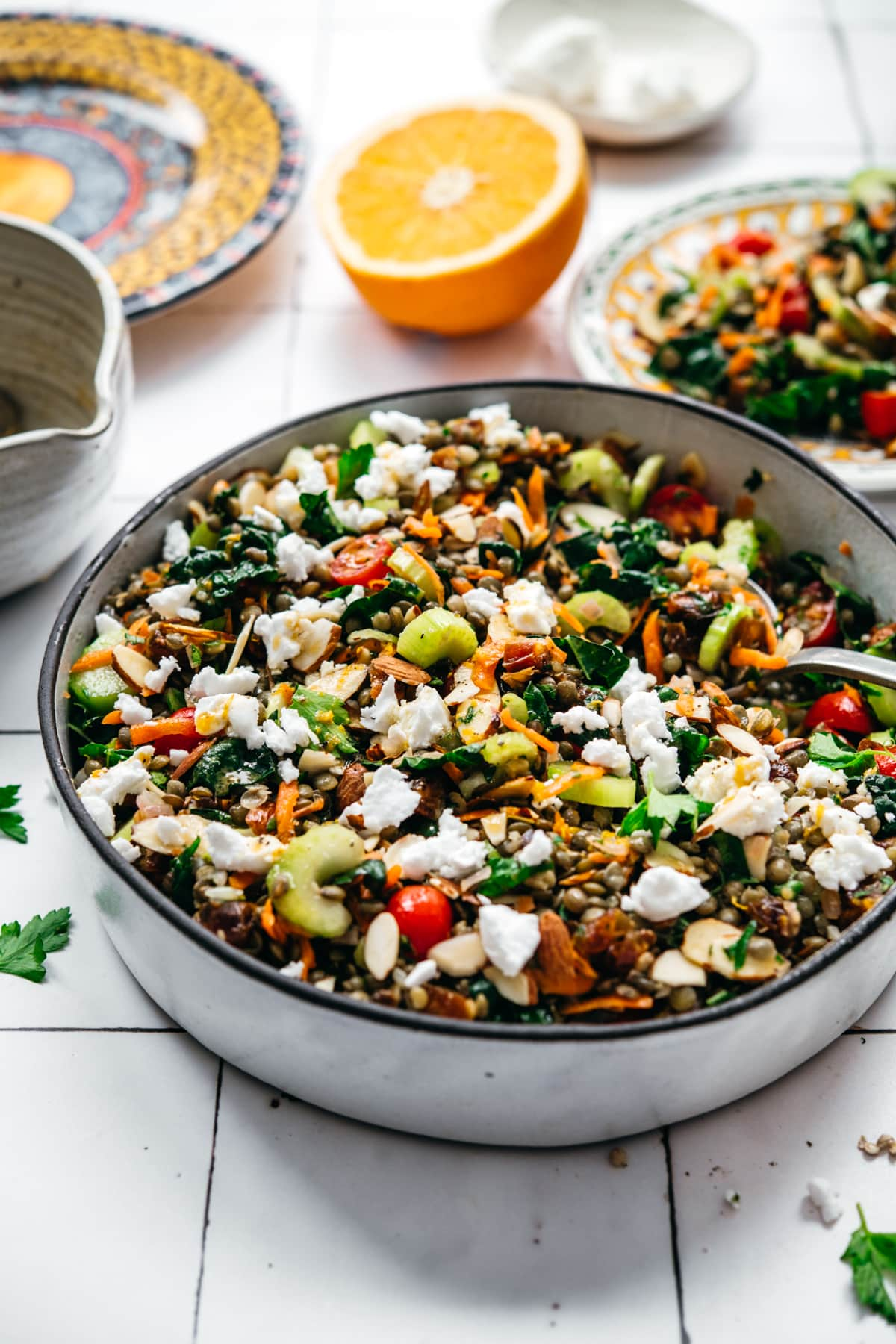 side view of vegan french lentil salad in a large bowl with serving spoon on white tile background.