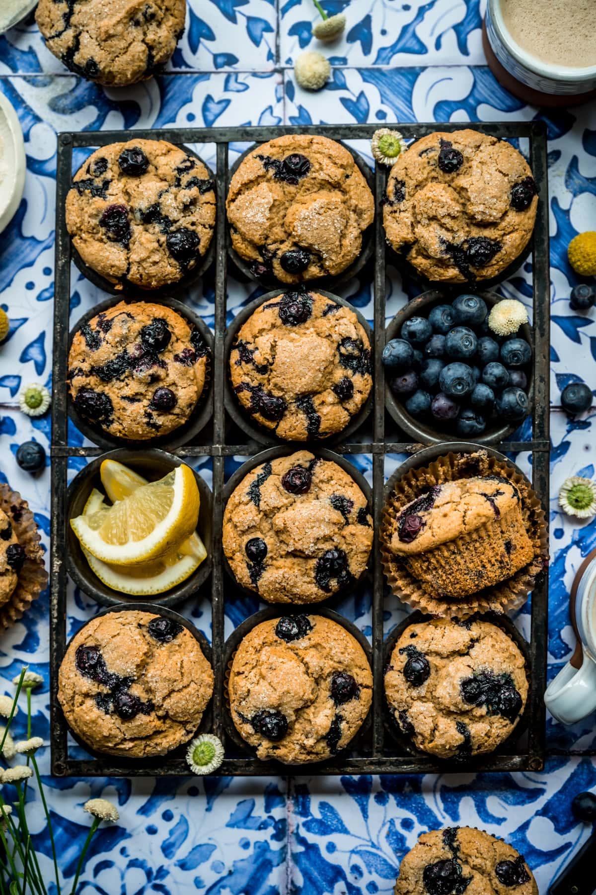overhead view of vegan blueberry muffins in antique muffin tin on blue tile backdrop.