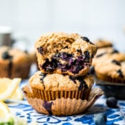 close up side view of two stacked vegan blueberry muffins with the top one cut in half.