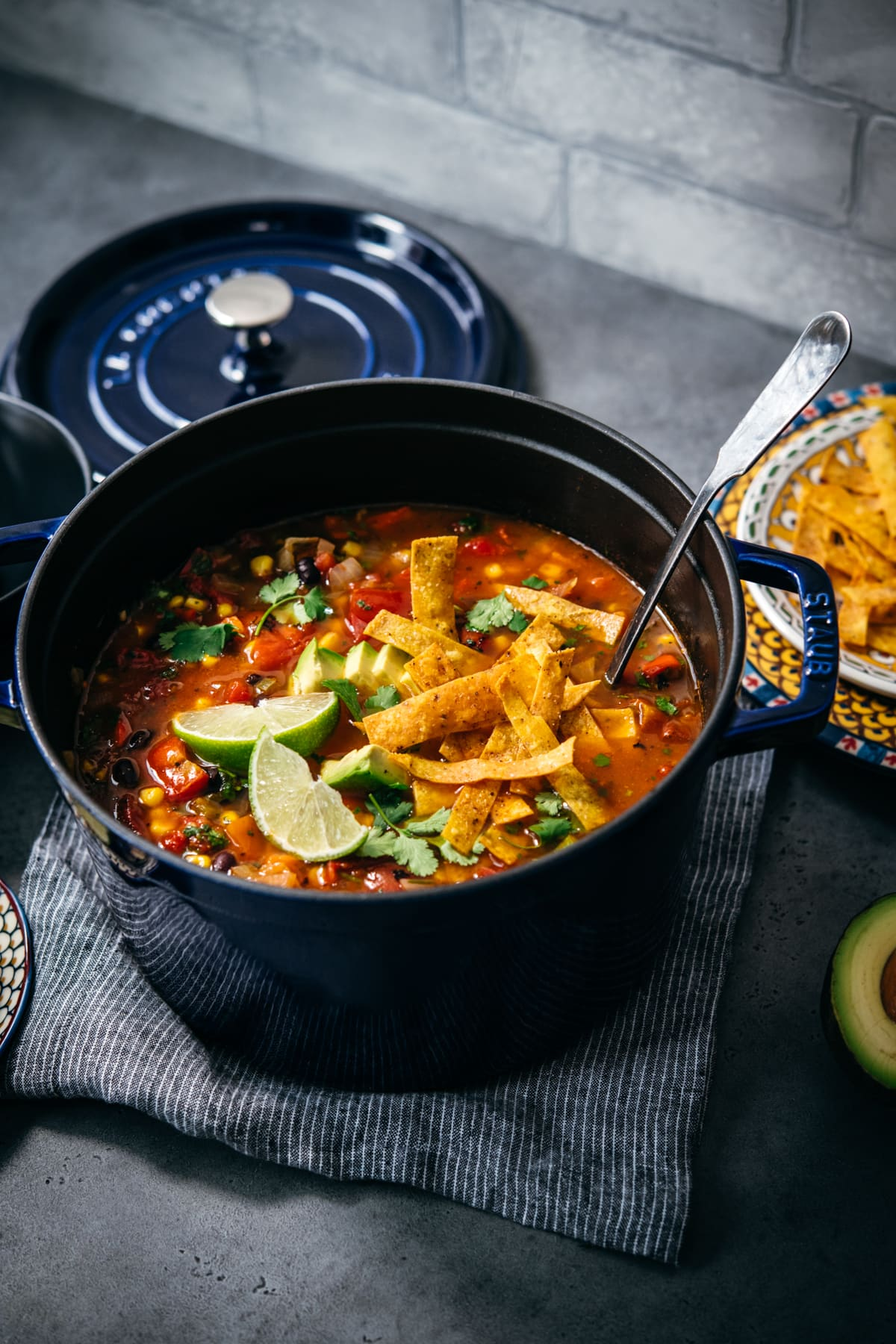 overhead view of vegan tortilla soup in large Staub pot topped with tortilla strips, avocado and cilantro.
